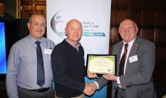 Cllr Brian Johnson presents the award to rowing club members
